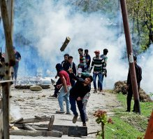 Srinagar: Protesters hurl large wooden logs towards Police personnel after clashes erupted over the killing of a youth in Narbal, Srinagar on Saturday. PTI Photo by S Irfan(PTI4_18_2015_000099B)
