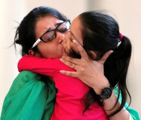 Uzma, an Indian woman who according to local media was forced to marry a Pakistani man, kisses her daughter after her arrival, in New Delhi, India May 25, 2017. REUTERS/Adnan Abidi - RTX37KYX